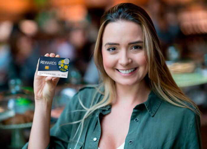 Moça mostrando um cartão de Como é a atuação na administração de Clubes de Desconto?