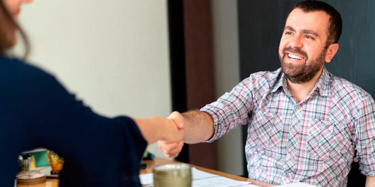 imagem com duas pessoas sorrindo e se cumprimentando em uma mesa de negócios necessário para fidelização de clientes